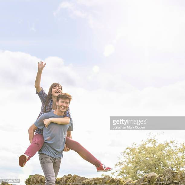 Young man giving piggyback ride to girlfriend in countryside under bright sunny sky