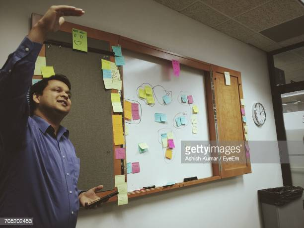 Young Man Giving Presentation In Board Room