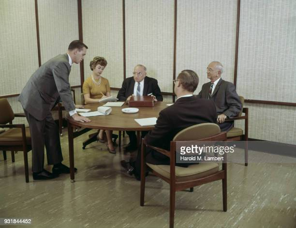Young man giving presentation to senior businessman with assistant standing besides
