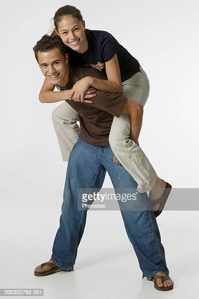 young man giving teenage girl (16-17) piggy back ride, posing in studio, portrait - lying on back stock pictures, royalty-free photos & images