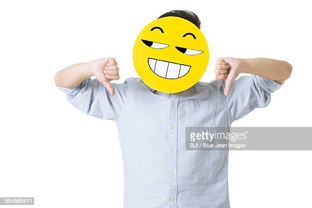 Young man giving thumbs down with happy emoticon face in front of his face