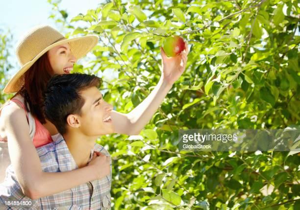 Young man giving woman a piggyback ride