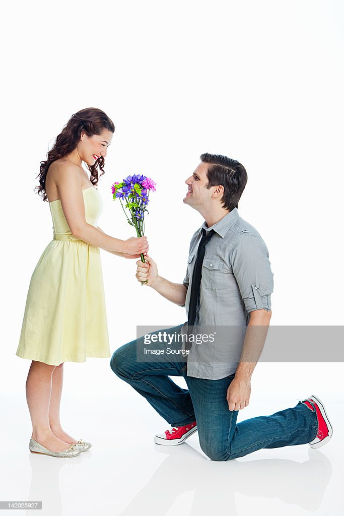 Young man giving woman flowers against white background : Stock Photo