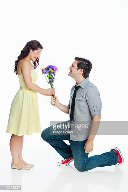 Young man giving woman flowers against white background