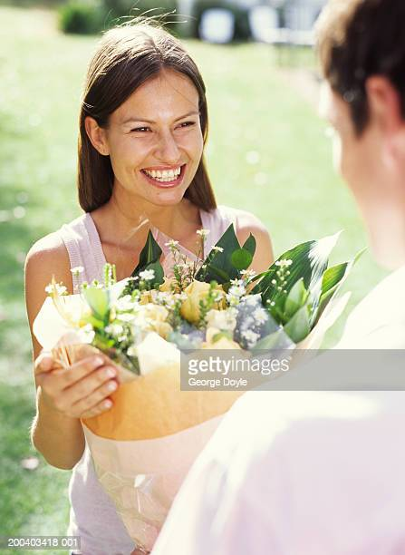 Young man giving woman flowers, elevated view