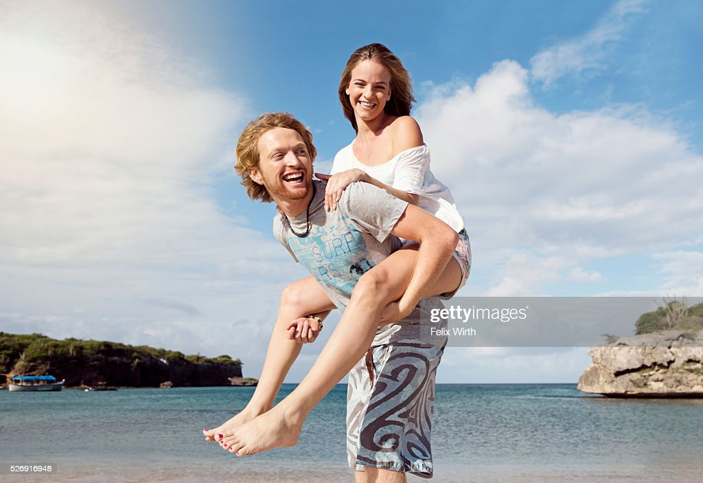 Young man giving woman piggyback ride on beach : Stock Photo
