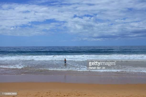 young man goes into the sea to swim - rafael ben ari imagens e fotografias de stock