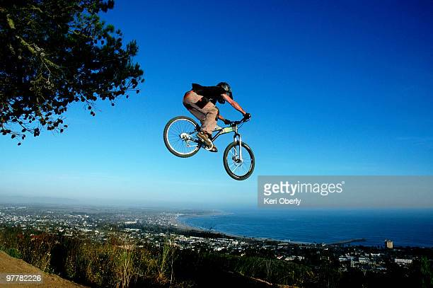 A young man goes off a jump on a mountain bike in the hills overlooking Ventura, California.