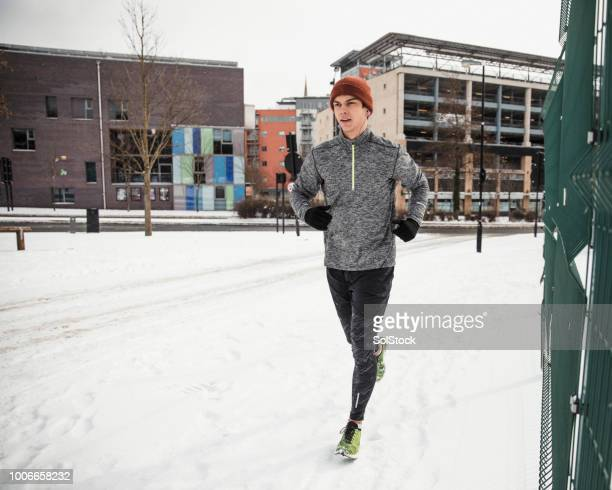 young man going for a run in the snow - 18 19 anos imagens e fotografias de stock