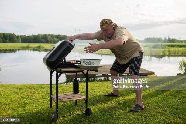 young man grilling by lake against sky - funny bbq stock pictures, royalty-free photos & images