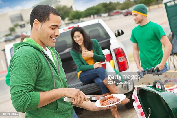 Young man grilling during tailgating party near football stadium