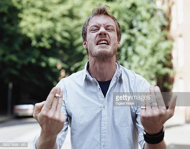 Young man grimacing and hand gesturing, outdoors, portrait