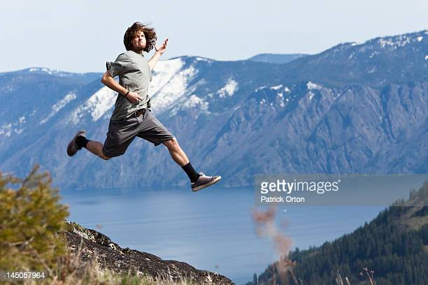 A young man grins as he jumps and does a air guitar above a mountain lake in Idaho.