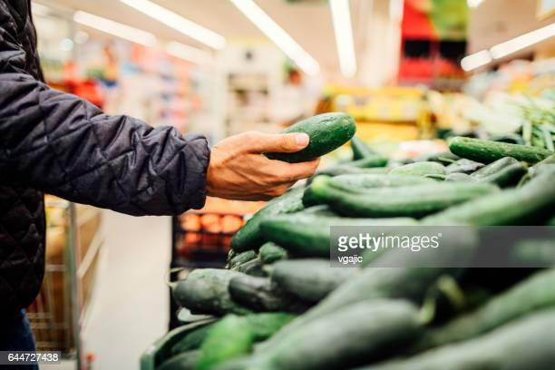 junger mann lebensmittel einkaufen - gurke stock-fotos und bilder
