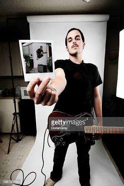 Young Man Guitarist Holding Polaroid of Himself