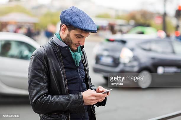 Jeune homme à l'aide de smartphones hélant un taxi à l'application.