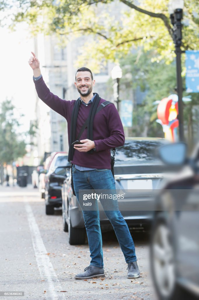 Young man hailing taxi on city street : Stock Photo