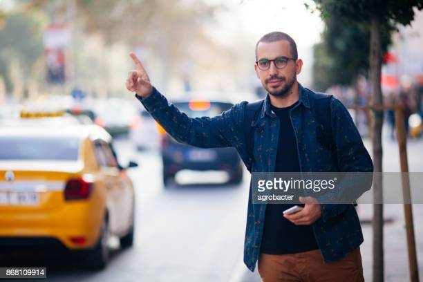 Young man hailing taxi on city street