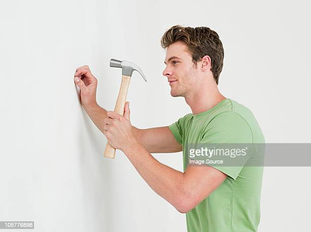 young man hammering nail into wall - hammer stock pictures, royalty-free photos & images