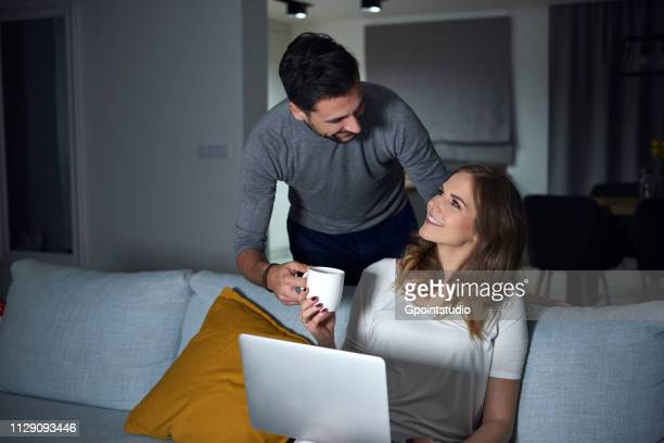 Young man handing coffee to girlfriend sitting on sofa in evening