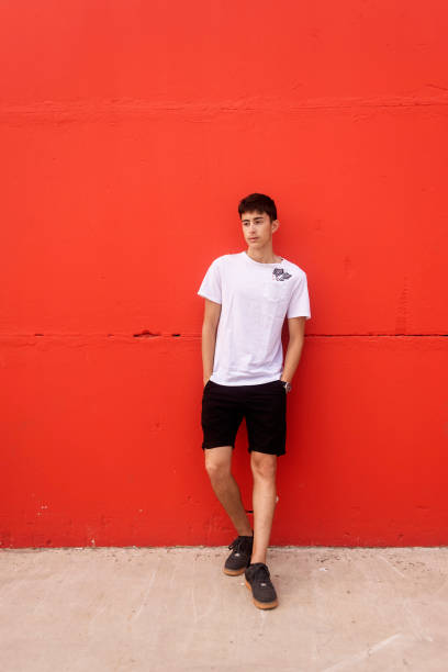 Young man hands on pocket, leaning on red wall