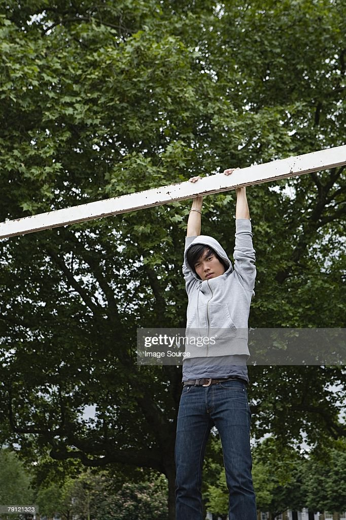 Young man hanging from a goalpost : Stock Photo