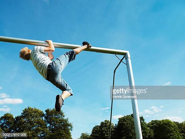 Young man hanging from crossbar, low angle view