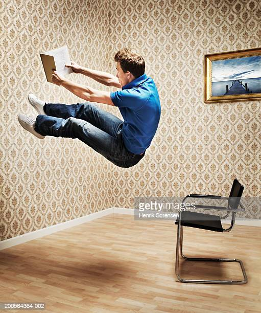 Young man hanging in air and reading book