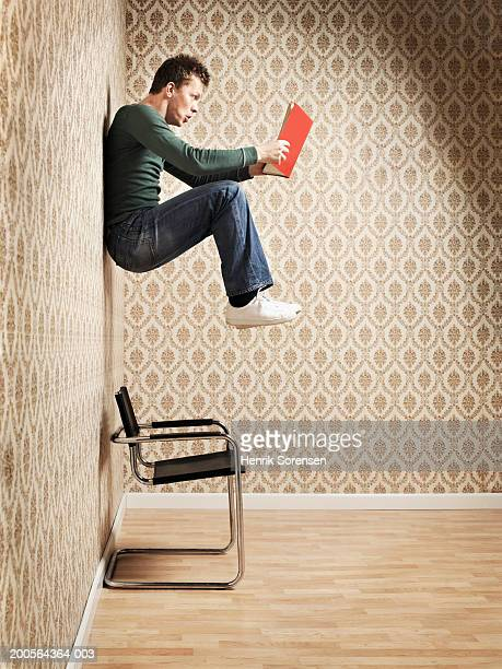 Young man hanging on wall and reading book, side view