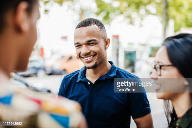 young man hanging out with friends in city - polo shirt stock pictures, royalty-free photos & images