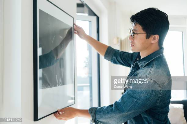 young man hanging picture on wall at home - design professional stock pictures, royalty-free photos & images
