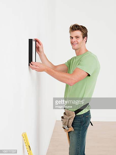 Young man hanging picture on wall