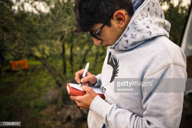 young man harvesting at vineyard writing notes - heshphoto stock pictures, royalty-free photos & images