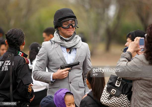 A young man has his snapshot taken wearing the goggles and kevlar helmet and holding the pistol of a police officer during the graduation ceremony of...