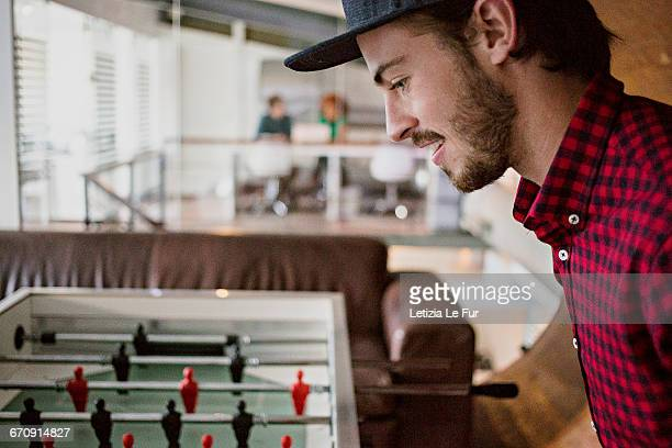 Young man having a break playing table football in office