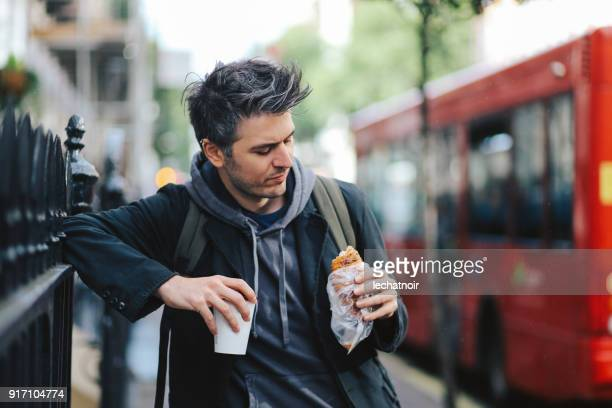 Young man having a coffee and a croissant on the go, in London, UK