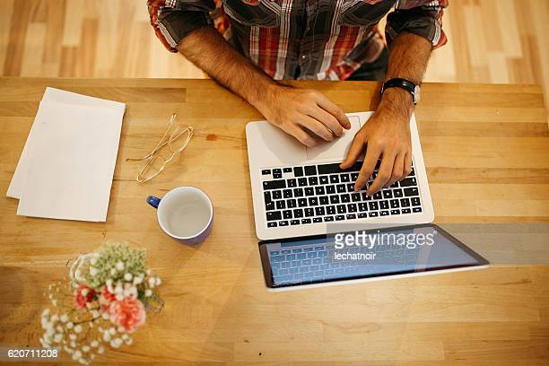 Young man having a coffee and working at home