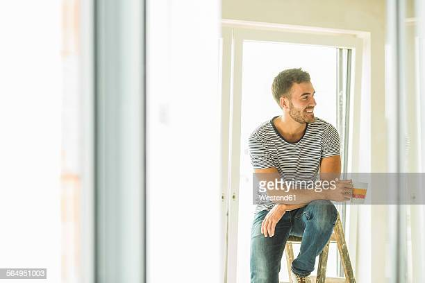 Young man having a coffee break from renovating