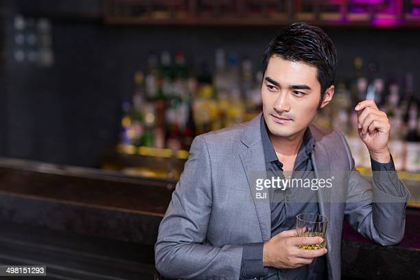 Young man having a drink at bar