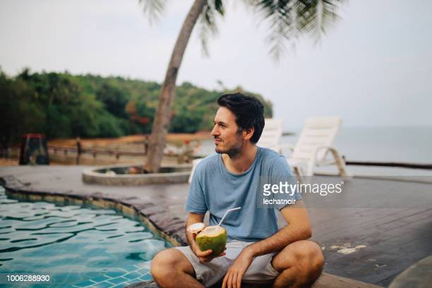 young man having a fresh coconut drink by the ocean on the island of koh lanta, thailand - coconut water stock pictures, royalty-free photos & images