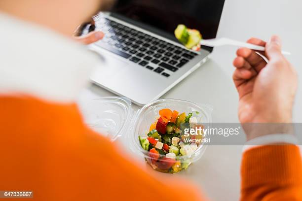young man having a salad at desk in office - convenience stock photos and pictures