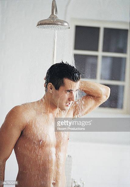 young man having a shower - homme sous la douche photos et images de collection