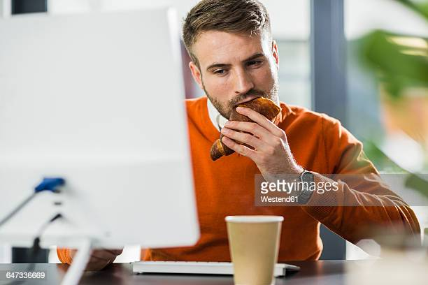 Young man having a snack at desk in office