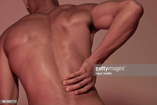 young man having back pains - liesbreuk stockfoto's en -beelden