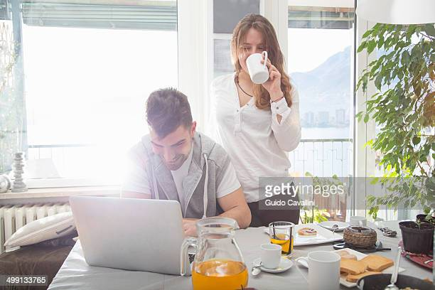 young man having breakfast and using laptop - coppia eterosessuale foto e immagini stock