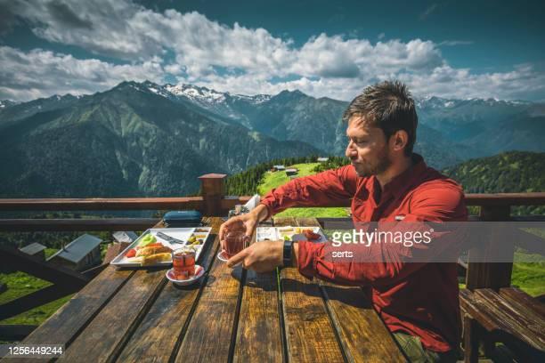 ポクト高原、カムルヘムシン、リゼ、トルコの黒海地域で風景を眺めた朝食をとっている若者 - トラブゾン ストックフォトと画像