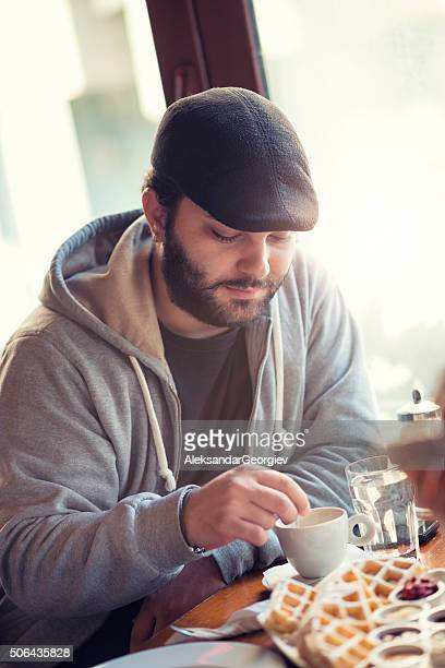 Young Man Having Coffee and Waffles for Breakfast at Restaurant