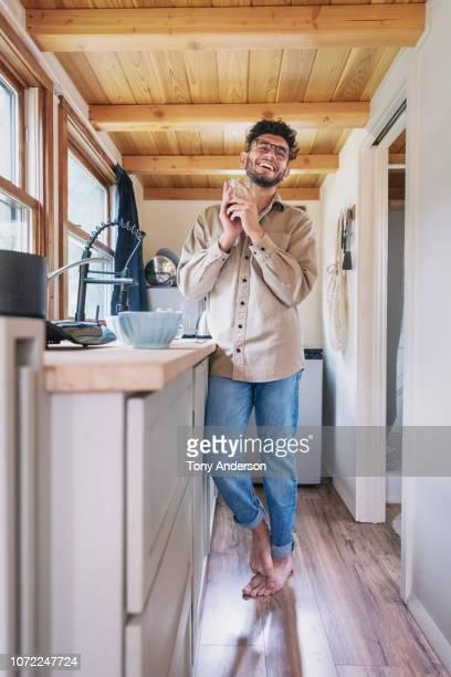 young man having coffee in kitchen of tiny house - wohngebäude innenansicht stock-fotos und bilder