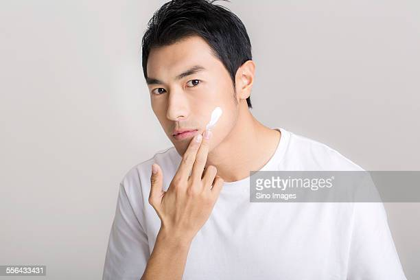 young man having facial treatment - image stock pictures, royalty-free photos & images