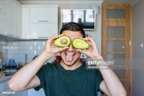young man having fun with avocado at the kitchen - cuisine humour photos et images de collection